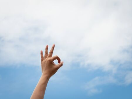 Okey. Woman hand OK sign against with blue sky and white clouds. Stock fotó
