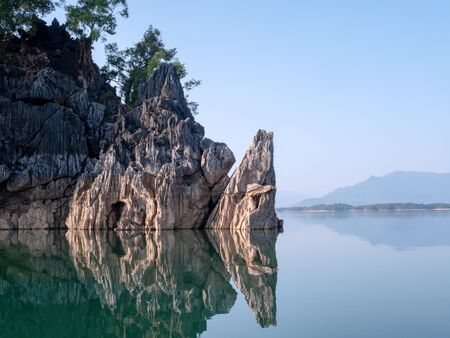 Rock mountain island reflect on lake water with clear blue sky. Calm and peace river.