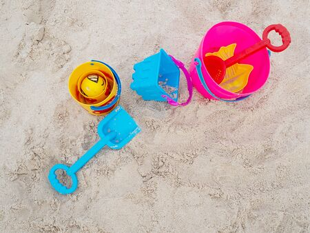 Colorful plastic children's beach toys on sand beach in summer day. Kids toys, bucket, shovel.