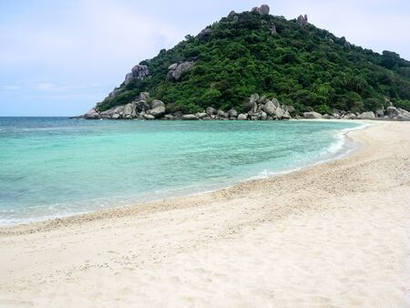 Idyllic tropical paradise beach white sand and crystal clear sea  blue sky with green hill Island.