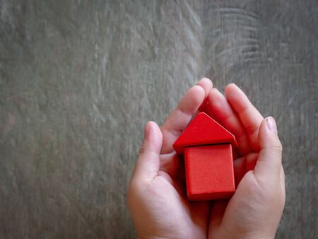 Child hands holding red model house, family, homeless, home loan and home protect insurance concept.