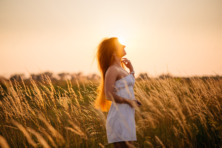 deployed: Young beautiful red-haired girl in a field at sunset, back to camera, deployed in profile