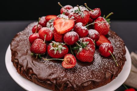 Tuscan chocolate cake with strawberries and cherries on dark background