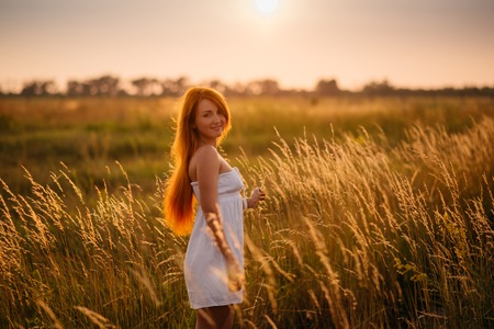 Young beautiful red-haired girl in a field at sunset, looking into the camera Stock Photo