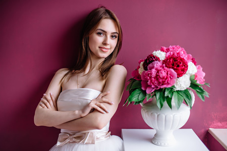 magenta dress: young beautiful bride with a bouquet of pink peony near the wall Stock Photo