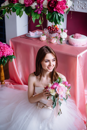young beautiful bride with a bouquet of pink peony