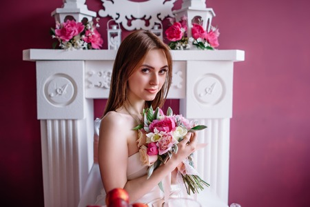 young beautiful bride with a bouquet of pink peony near the white fireplace