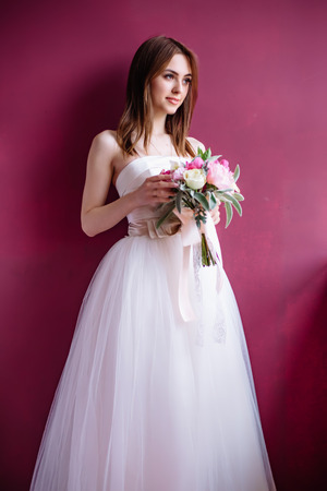 young beautiful bride with a bouquet of pink peony near the wall Stock Photo