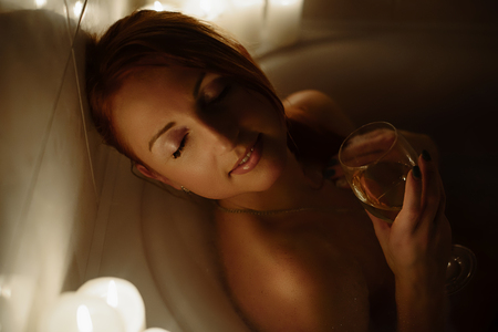woman bath: Young beautiful red-haired woman relaxes in the bath by candlelight Stock Photo