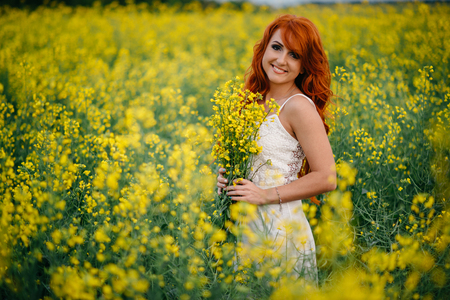 glades: Young beautiful red-haired woman in a blooming rapeseed field at sunset