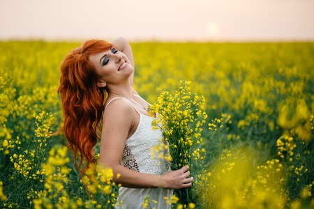 Young beautiful red-haired woman in a blooming rapeseed field at sunset