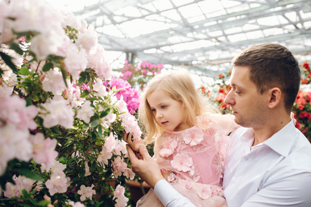 A young father holding a small daughter in his arms, who admires flowers in a spring flowering garden