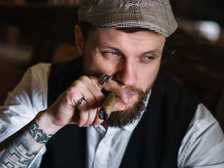 cuff: A young bearded man smoking a cigar in a pub Stock Photo
