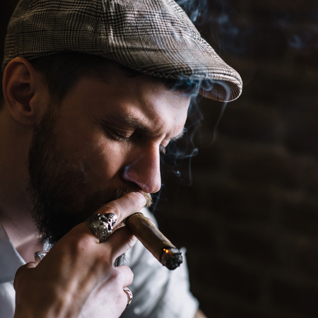 cuff link: A young bearded man smoking a cigar in a pub Stock Photo