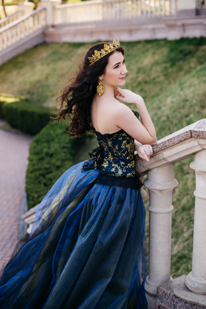Young woman in a luxurious blue dress with a long train on the architecture background Stock Photo