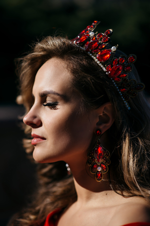 ruche: Young woman with a luxurious crown on her head and in a red dress, close-up