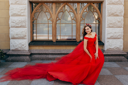 ruche: Young woman in a luxurious red dress with a long train on the architecture background