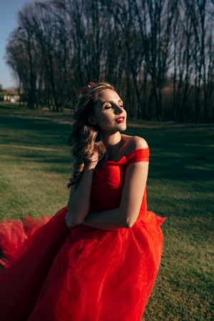 ruche: Young woman in a luxurious red dress with a long train On the green lawn