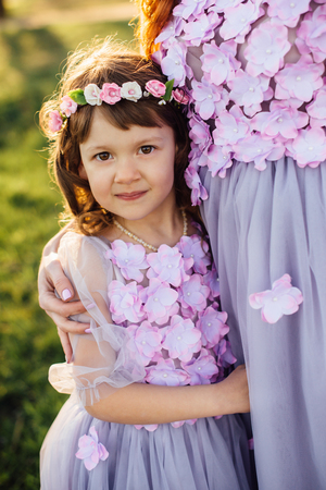 A little girl in a fairy purple dress and wreath cuddles to her mother