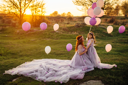 Young beautiful red-haired mother with her daughter, dressed in luxurious purple dresses, walking with balloons in nature in the sun