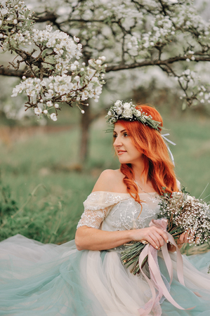 Young red-haired woman in a luxurious dress sits on the grass in a blooming garden Stock Photo