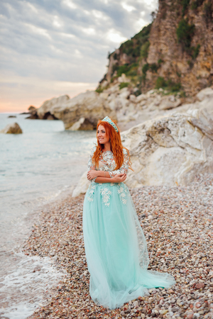Young beautiful red-haired woman in a luxurious dress standing on a rocky shore of the Adriatic Sea