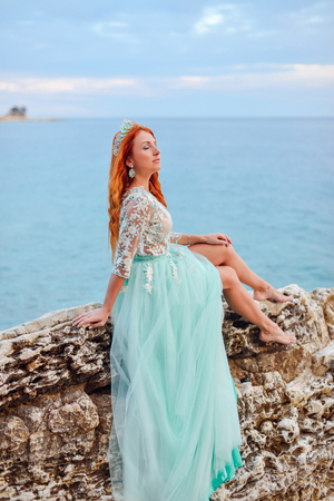 Young beautiful red-haired woman in mint dress sits on a large stone on the shore of the Adriatic Sea Stock Photo
