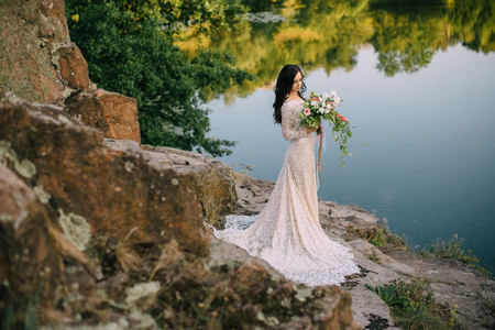 tenderly: Young bride in wedding dress standing on rocky river bank, sunset Stock Photo