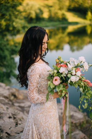 tenderly: young bride stands on the river bank with a bouquet in her hands
