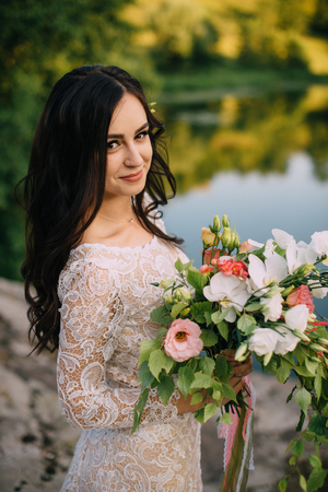 young bride stands on the river bank with a bouquet in her hands