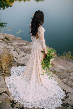 tenderly: young bride stands on the river bank with her back to the camera