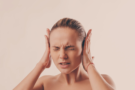 portrait of a young woman who closes her ears with her hands because of strong noise Stock Photo