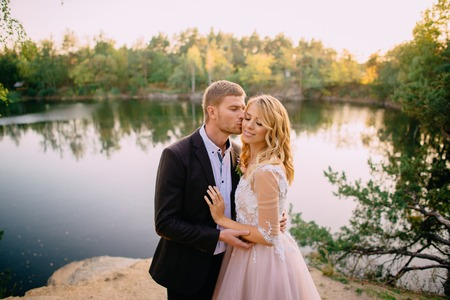 groom kisses a happy bride against the backdrop of nature at sunset