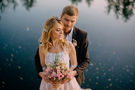 groom tenderly embraces the bride against the background of nature at sunset, close-up
