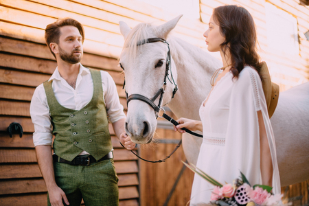 newlyweds look at each other holding horse 스톡 콘텐츠