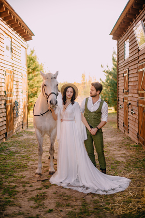 stylish couple standing and hugging near stables