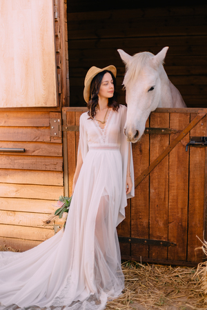 bride dressed boho style standing near horse Banque d'images - 115132048