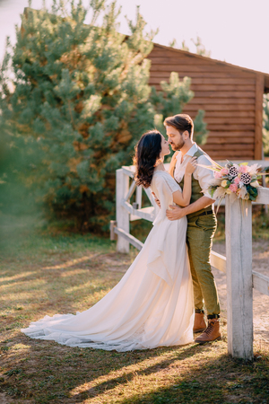 Newlyweds in cowboy style standing and hugging on ranch, summer day Фото со стока