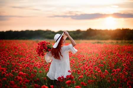Red-haired woman in white hat stands in flowered field of red poppies with his back to camera Stock Photo