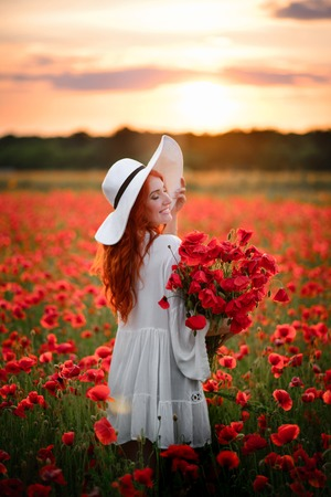 Happy Young beautiful female with bouquet of red poppies stands in flowered field at sunset