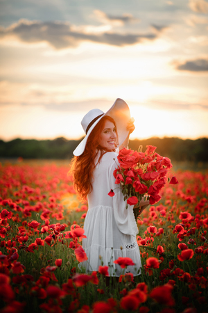 Young beautiful female with bouquet of red poppies stands in flowered field at sunset