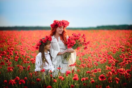 Happy mother and little daughter stand in blooming field in wreaths of wild poppy flowers