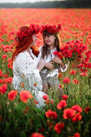 Young mother with little daughter collect red poppy flowers in a blossoming field, close up Stock Photo