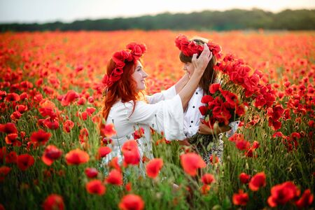 Young mother puts wreath of poppy flowers on her daughters head, close up Stock Photo