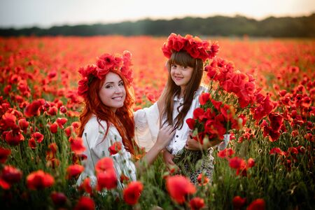 Happy mother and little daughter sitting in blooming field in wreaths of wild poppy flowers