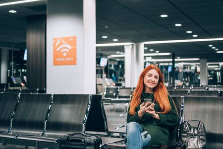 Woman uses free internet in airport terminal Banque d'images - 133676339