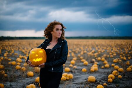 Woman in black clothes holds pumpkin in her hands, halloween concept Banque d'images - 133677269