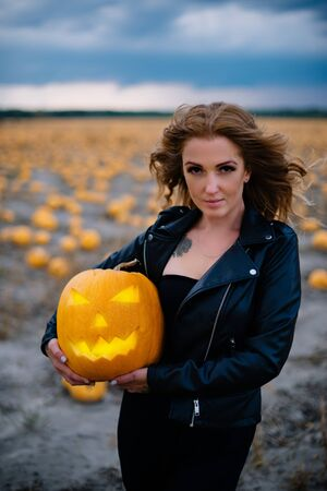 Woman in black clothes holds pumpkin in her hands, halloween concept Banque d'images - 133677268