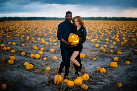 couple standing in pumpkin field and holding scary face pumpkin, concept halloween Banque d'images - 133677271