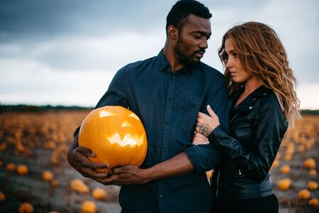 Couple standing in pumpkin field, man is holding scary face pumpkin, concept halloween Banque d'images - 133677273